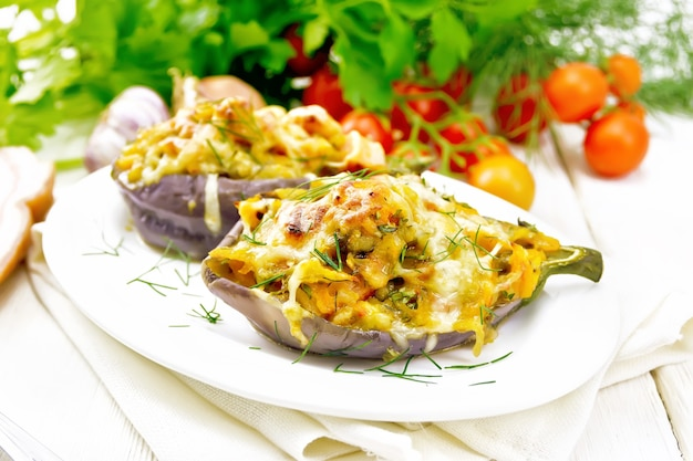 Stuffed eggplant with smoked brisket, tomatoes, onions, carrots with garlic, cheese and herbs in a plate on a kitchen towel on background of light wooden board