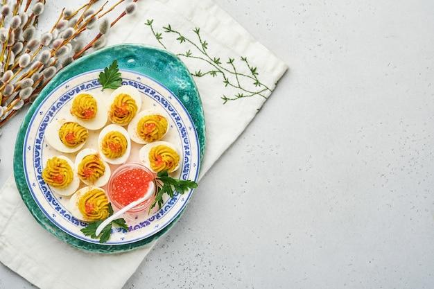 前菜のイースター テーブル用のプレートにイクラとパプリカを詰めた卵の詰め物