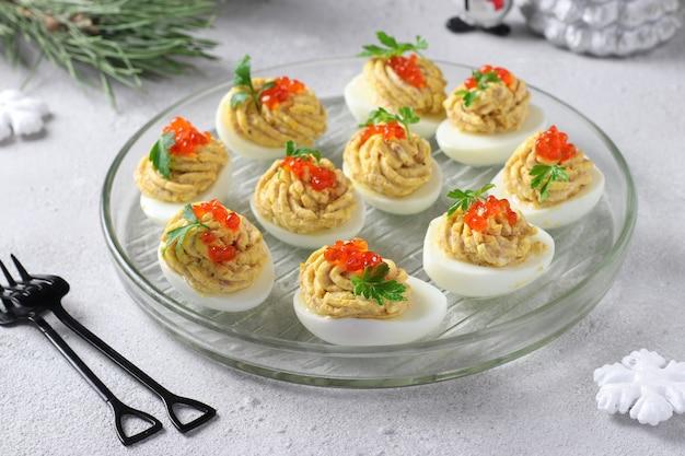 참치와 치즈로 채워진 계란은 붉은 캐비아로 장식되어 있으며 밝은 회색 배경에 축제 간식이 있습니다.