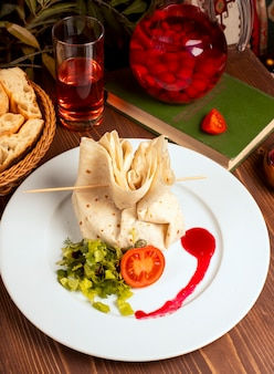 Stuffed filled lavash with tomato and vegetables in white plate.