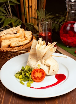 Stuffed filled lavash with tomato and vegetables in white plate