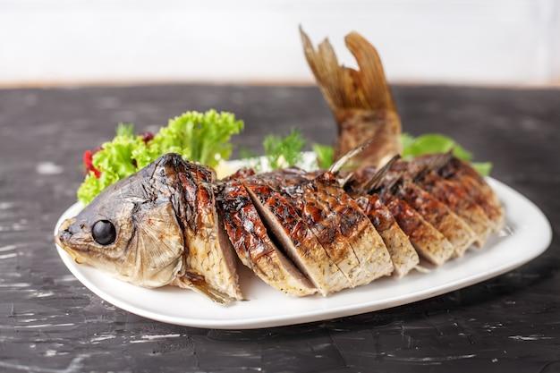 Фаршированная рыба с листьями салата, перцем и лимоном. концепция еды