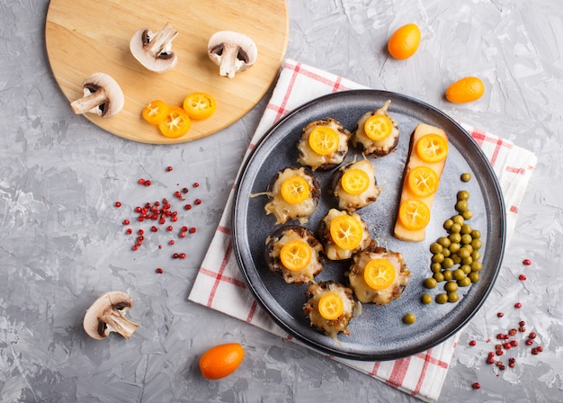 Stuffed fried champignons with cheese kumquats and green peas on a gray concrete background  close up