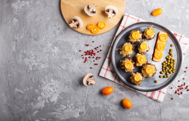 Stuffed fried champignons with cheese, kumquats and green peas on a gray concrete background