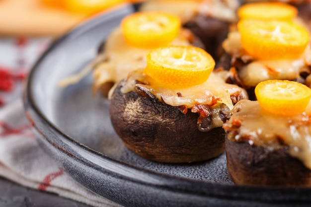 Stuffed fried champignons with cheese, kumquats and green peas. side view, close up, macro.