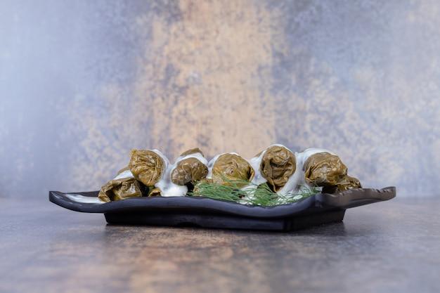 ぶどうの葉の詰め物は、ヨーグルトと一緒に皿にドルマを残します。