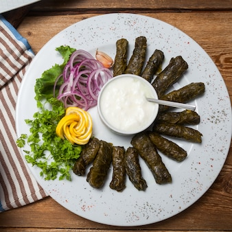 Stuffed grape leaves with decorations in a plate on wooden background, top view.