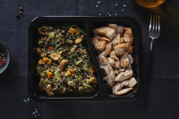 カシューナッツと調理済みの鶏の胸肉を詰めたグリーンケールサラダをランチボックスでお召し上がりいただけます。健康的な生活様式。