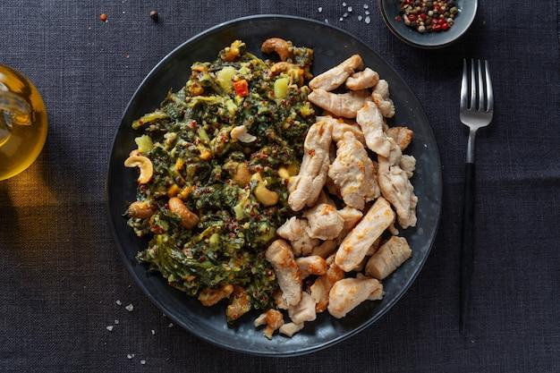 カシューナッツと調理済みの鶏の胸肉を詰めたグリーンケールサラダをダークプレートでお召し上がりいただけます。健康的な生活様式。