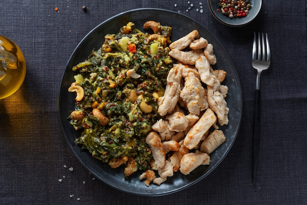 Stuffed green kale salad with cashew and cooked chicken breast served on dark plate. healthy lifestyle.