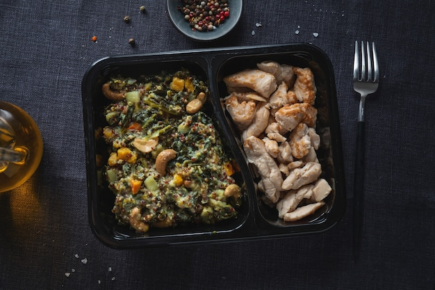 Stuffed green kale salad with cashew and cooked chicken breast served in lunch box. healthy lifestyle.