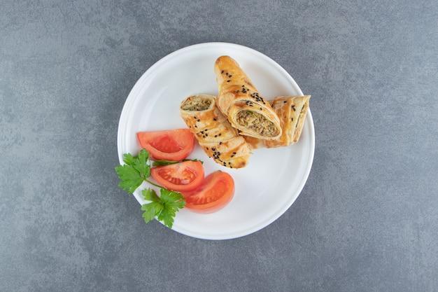 Фаршированная выпечка с мясом на белой тарелке.