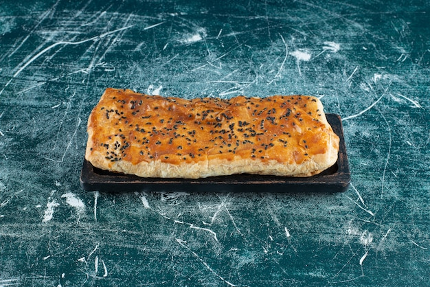 Stuffed pastry with sesame seeds on marble surface.