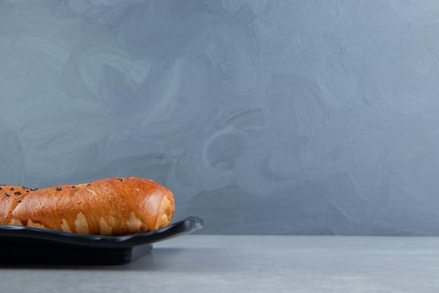 Фаршированное тесто с кунжутом на черной тарелке.