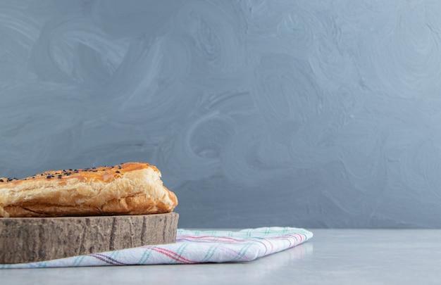 Pasta ripiena con semi di sesamo su pezzo di legno.