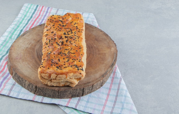 Stuffed pastry with sesame seeds on wood piece.
