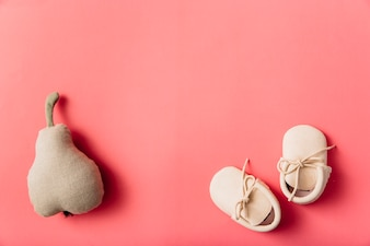 Stuffed pear fruit and pair of baby's shoes on colored background