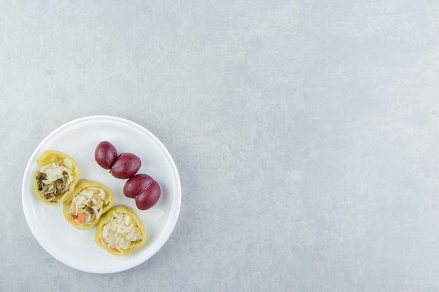 박제 고추와 흰색 접시에 자 두입니다.