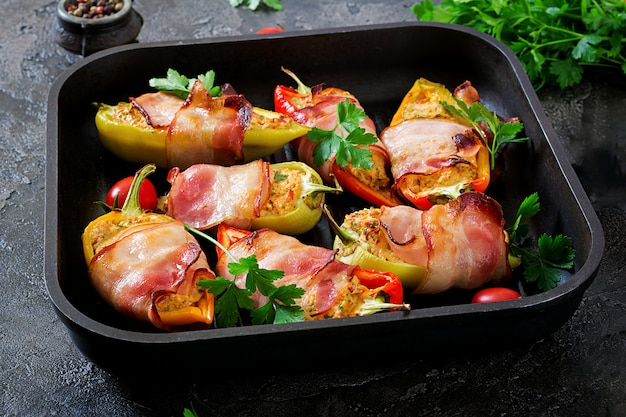 Stuffed peppers with cottage cheese and bacon in pan on the table.