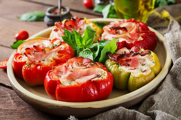 Stuffed peppers with cottage cheese and bacon in plate on the wooden table