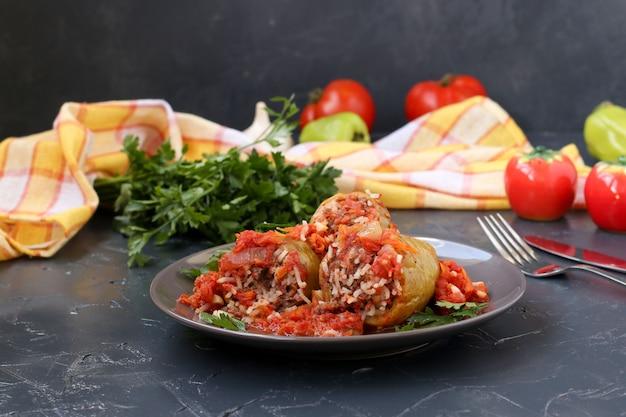 暗闇の中でプレートにある肉、米、トマトソースのピーマンの詰め物