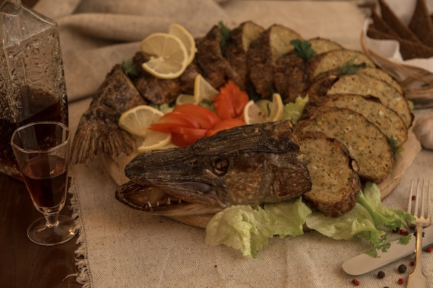 Stuffed pike with vegetables and greens.
