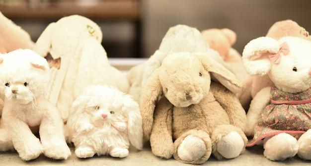 Мягкие плюшевые игрушки зайцы на полке.