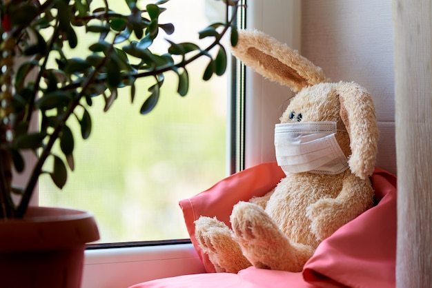 A stuffed rabbit in a mask sits on pillows in a blanket by the window.