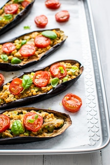 Stuffed roasted eggplant boats with tomatoes