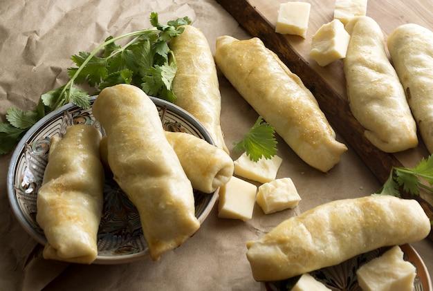 Фаршированные ролями домашняя выпечка, кусочки сыра и вкусная ежевичная выпечка на деревянной вырезке ...