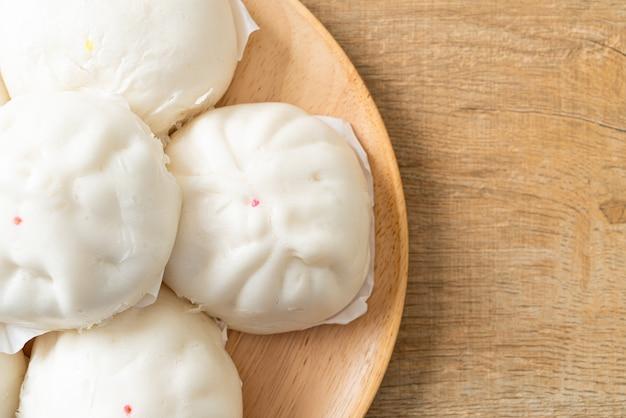 Фаршированная паровая булочка на деревянной тарелке - стиль китайской кухни
