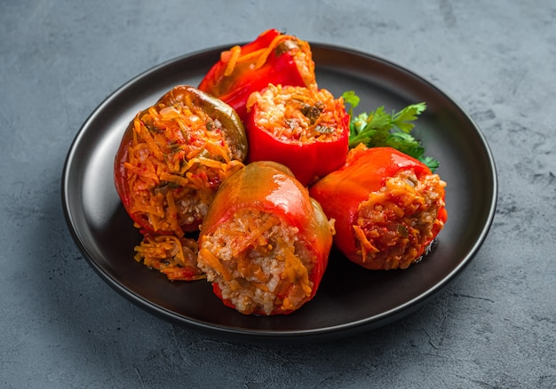 Stuffed stewed bell peppers on a black plate on a dark background