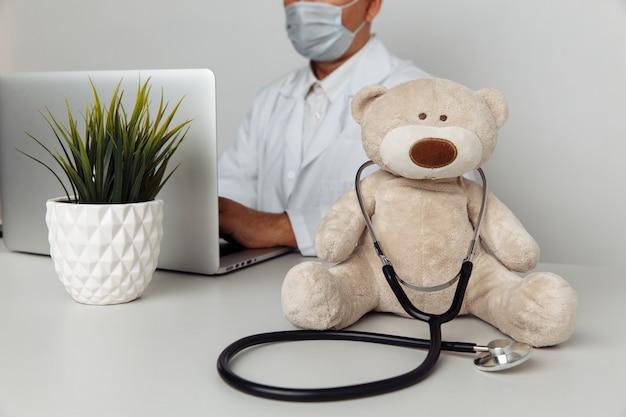 小児科医のオフィスで聴診器を備えたぬいぐるみのテディベア。子供のヘルスケアの概念。