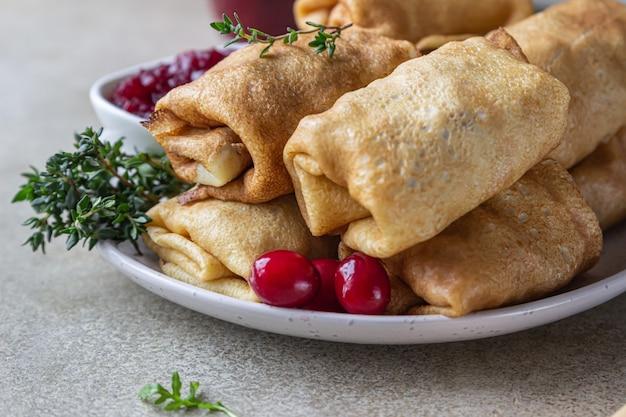 고기, 매운 크랜베리 소스 및 arugula로 채워진 얇은 팬케이크 또는 크레페.