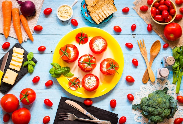 Stuffed tomatoes with cheese and different vegetables, on a wooden table,