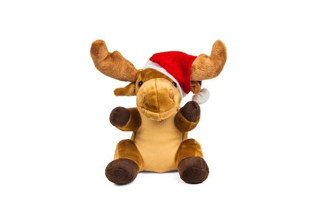白い壁に分離されたサンタクロースの帽子のぬいぐるみクリスマス鹿