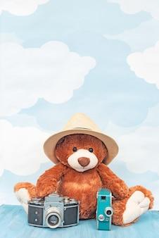 Мягкий игрушечный мишка сидит возле старой фотоаппарата и ретро видеокамеры на пастели голубого неба.