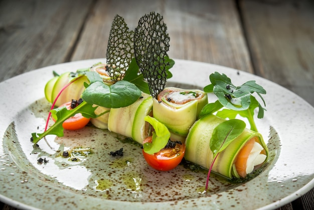 Stuffed zucchini rolled with cream cheese on complex background, on a wooden background