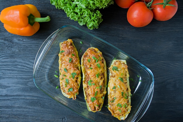 Stuffed zucchini with minced meat and grated cheese in a glass baking sheet.