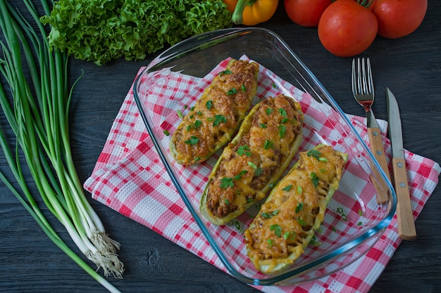 Stuffed zucchini with minced meat and grated cheese in a glass baking sheet
