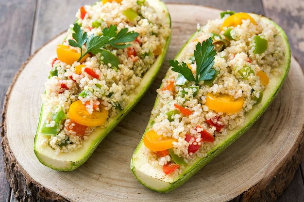 Stuffed zucchini with quinoa and vegetables on wooden table