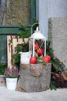 Пень с елочными украшениями возле дома