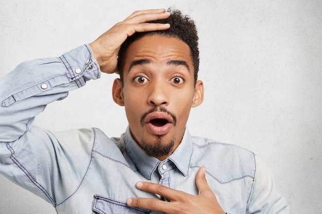 Ошеломленный изумленный африканский студент смотрит на расписание с удивленными глазами и видит нечто невероятное.