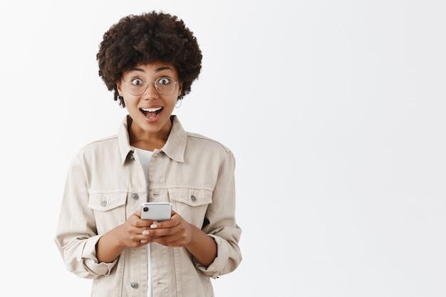 ベージュのシャツとスマホをかざしたスマートフォンで息を切らして感心と興奮で見つめる、驚くほど見栄えのよいアフリカ系アメリカ人のボーイッシュな女の子