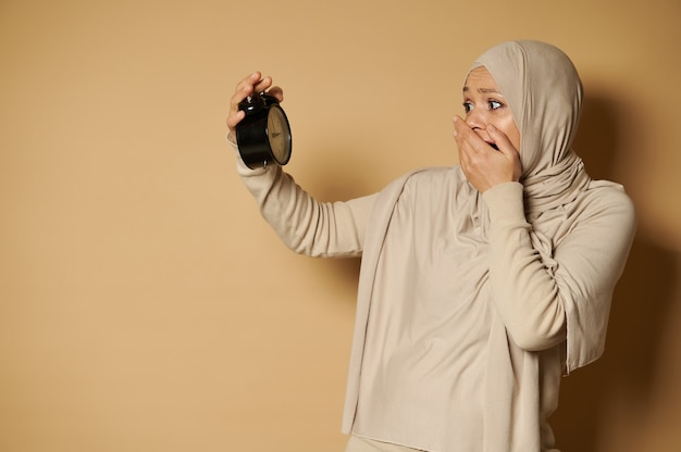 A stunned arab woman with a covered head in a hijab holds an alarm clock in her hands and looks at it in horror