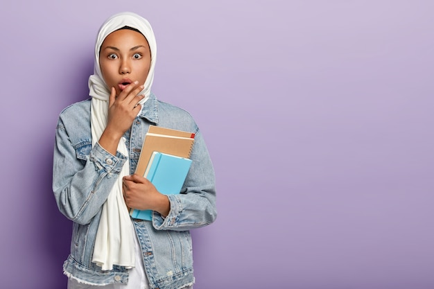 기절 한 아라비아 학생은 고등학교에 다니고, 피부가 검고, 노트를 쓸 수있는 메모장을 들고, 머리에 흰 베일을 쓰고, 자신의 종교적 전통을 가지고 있으며, 실내에서 포즈를 취합니다.