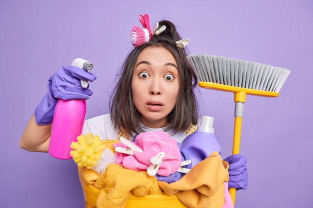 Stunned asian woman stares bugged eyes has clothespins and brush on hair holds broom