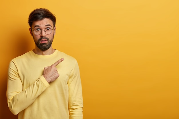 깜짝 놀란 남자는 믿을 수없는 프리젠 테이션을 선전하고, 오른쪽 상단의 빈 카피 공간을 가리키고, 경이로움에서 헐떡이며, 벽과 한 톤의 노란색 점퍼를 착용하고, 제품을 광고합니다.