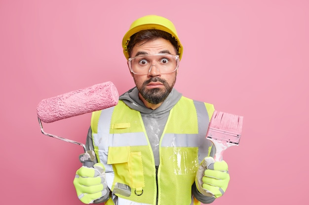 Stunned bearded handyman holds paint roller and brush uses special tools involved in building and repairing wears protective helmet and uniform
