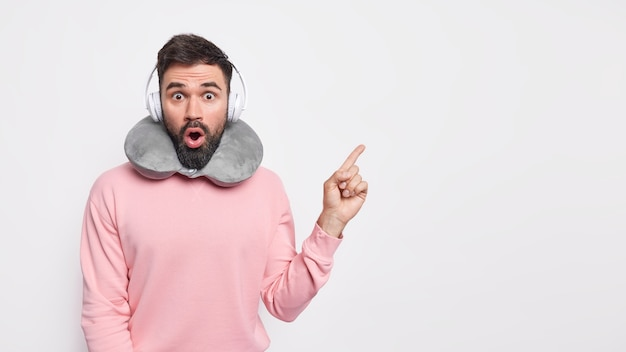 Stunned bearded speechless man has thick beard points away on copy space promots something unbelievable wears comfortable pillow around neck uses headphones for listening music